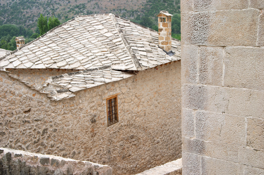 Detail of a narrow alley, stone house, with traditional stone tile slate roof. Pocitelj historic Muslim and Christian village near Mostar. Federation Bosne i Hercegovine. Bosnia Herzegovina, Europe.