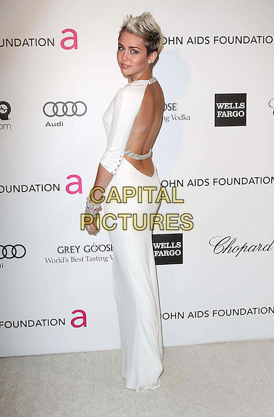 Miley Cyrus (wearing Azzaro).The 21st Annual Elton John AIDS Foundation Academy Awards Viewing Party held at The City of West Hollywood Park in West Hollywood, California, USA..February 24th, 2013.oscars full length dress white long sleeves diamond bracelets chains straps backless  side looking over shoulder .CAP/ADM/KB.©Kevan Brooks/AdMedia/Capital Pictures.