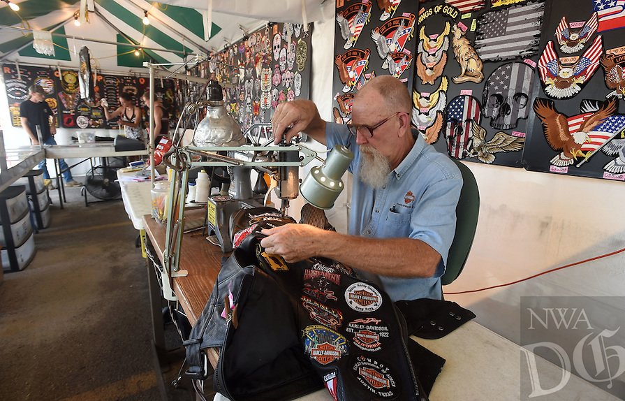NWA Democrat-Gazette/MICHAEL WOODS &bull; @NWAMICHAELW<br /> Jim Shockley with Sootos out of Canton Texas, sews a patch onto a bikers jacket Wednesday, September 21, as bikers begin to arrive for the 17th annual Bikes Blues and BBQ motorcycle rally in Fayetteville.  Wednesday was the first day of the event that runs through September 24th with activities going on everyday on Dickson Street, Baum Stadium, The Washington County Fairgrounds and Arvest Ballpark in Springdale.