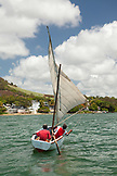 MAURITIUS, young men in a sailboat leave the Ilet Mangenie and enter the mouth of the Rhone River, East Coast