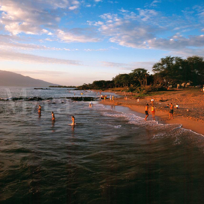 Swimmers at the beach at sunset. swimming, seashore. Kihei Hawaii, Kameole Beach.