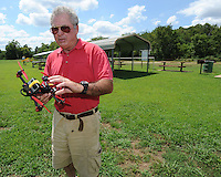 NWA Democrat-Gazette/ANDY SHUPE<br /> Bill Corley of Fayetteville assembles his radio-controlled racing quad copter Thursday, Aug. 13, 2015, at Hank Chenault Field in Combs Park in Fayetteville. Corley, a former commercial pilot, just purchased the craft and was trying it out for the first time.
