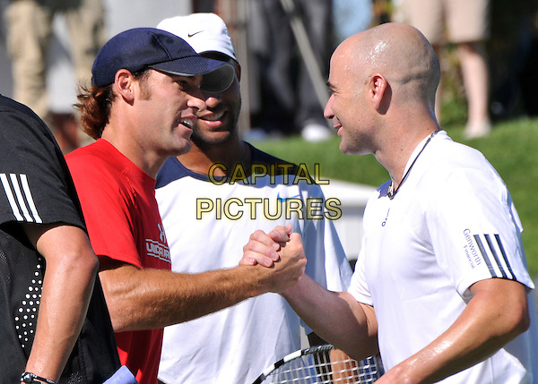 ROBBY GINEPRI & ANDRE AGASSI .The Bryan Brothers? All-Star Tennis Smash 2008 at the Sherwood Country Club, Thousand Oaks, California, USA, .27th September 2008.sport game sports playing half length red top t-shirt cap hat  shaking hands .CAP/ADM/BP.©Byron Purvis/Admedia/Capital PIctures