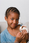 7 year old girl holding pet guinea pig vertical