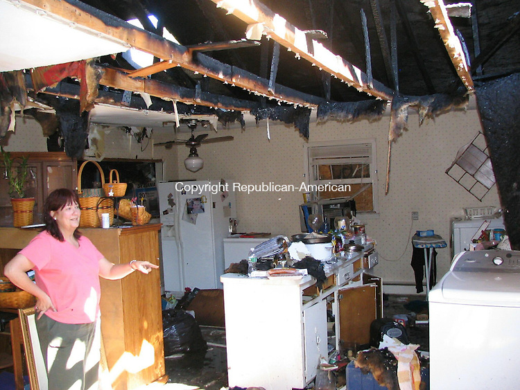 Wolcott, CT - 23 Sept. 2008 - 92308AL03 - Barbara Croft searches through the remains of her kitchen after a fire destroyed her apartment Monday night,