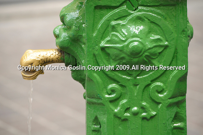 A water fountain that has just been painted bright green and that has a fish head for a spout in Como on Lake Como, Italy.