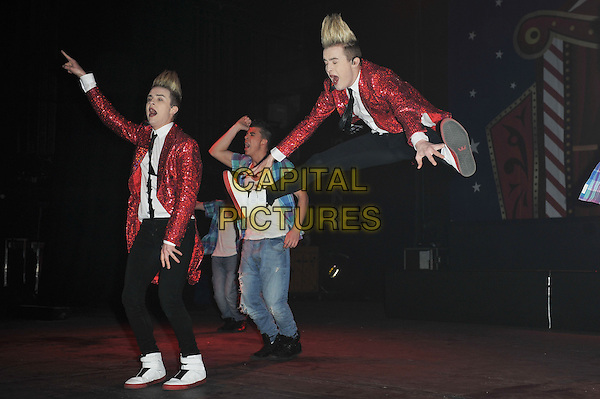 Jedward (John & Edward Grimes).Performing live in concert, Hammersmith Apollo, London, England. .6th December 2011.stage gig performance performing music on full length black trousers red sequins sequined suit jacket white shirt black tie dance dancing side profile legs jump jumping gesture mouth open singing singing.CAP/MAR.© Martin Harris/Capital Pictures.