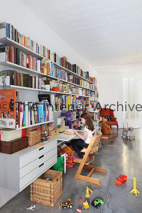 In the play area, work stations break up the shelves of books that run the length of one wall