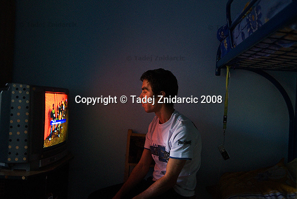 Boy watches television in his room in the apartment that Fundatia COTE provides for teenagers in transition from institutions to independent life. Iasi, Romania.