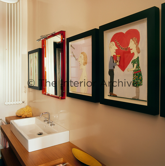 A red framed mirror and cartoon artworks hang on the wall above a bathroom washbasin set on a wood shelving unit.
