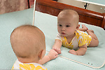 4 month old baby girl looking at self in mirror
