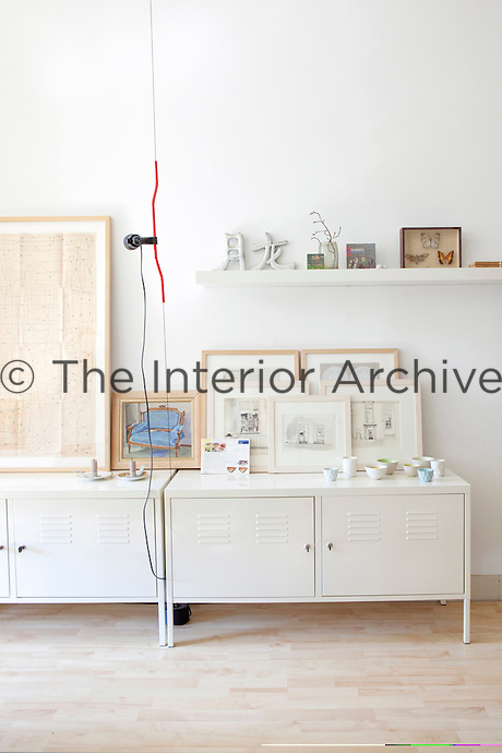 A collection of drawings is displayed on top of metal filing cabinets in the living room