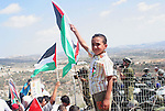 """Palestinian child hang the palestinian and israeli flag together on his shirt and waved the palestinian flag in front of israeli soldiers as villagers and peace activist celebrate the decision by the Israeli Supreme Court over the route of the controversial separation barrier being constructed by Israel in the occupied West Bank village of Bilin several kilometers from the city of Ramallah. Israel's Supreme Court ordered the state to re-route a section of its West Bank barrier at the village that has become a potent symbol of Palestinian opposition to the construction. The court ruled that the route of the separation barrier in the Bilin area was """"highly prejudicial"""" to the villagers and demanded that the government map out an alternative route """"within a reasonable period""""."""