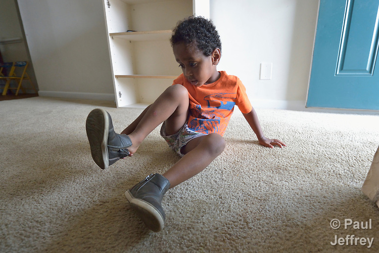 Three-year old Youel, a resettled refugee from Eritrea, puts on his shoes as he prepares to go outside to play in Durham, North Carolina. The boy and his mother were resettled in Durham by Church World Service, which resettles refugees in North Carolina and throughout the United States.<br /> <br /> Photo by Paul Jeffrey for Church World Service.