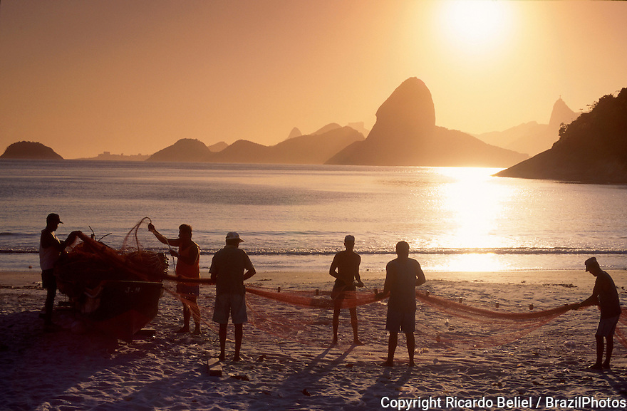Fishermen work in Niterói with a nice view of Rio de Janeiro mountains including Sugar Loaf and Corcovado ( Christ the Redeemer statue ), Brazil.