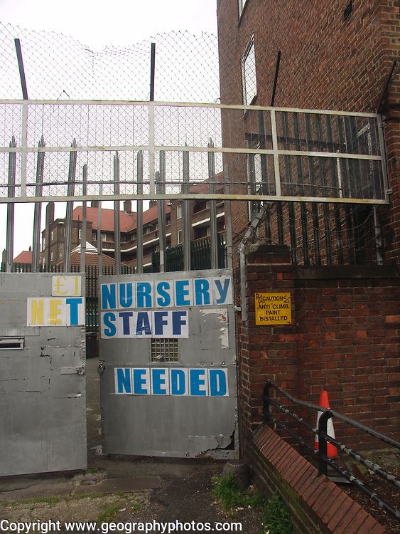 A51P89 Nursery staff needed poster on metal doors with security fencing and wire London England