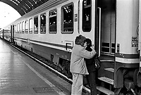 Milano, stazione centrale. Treno in partenza, un uomo e una donna si baciano --- Milan, central station. Train leaving, a man and a woman kissing