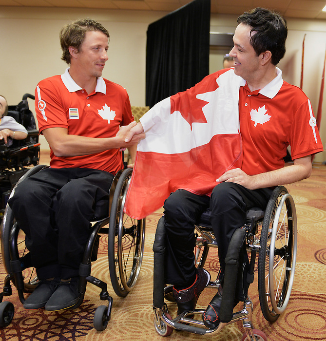 Toronto, ON - Aug 5 2015 - Sochi 2014 Closing Ceremonies flag bearer Josh Dueck hands of the Canadian Flag to Marco Dispaltro after being names as the Toronto 2015 Opening Ceremonies flag bearer. (Photo: Matthew Murnaghan/Canadian Paralympic Committee)
