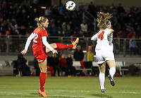 BOYDS, MARYLAND - April 06, 2013:  Stephanie Ochs (22) of The Washington Spirit boots the bal laway from Kristen McNabb (14) of the University of Virginia women's soccer team in a NWSL (National Women's Soccer League) pre season exhibition game at Maryland Soccerplex in Boyds, Maryland on April 06. Virginia won 6-3.