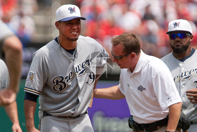 July 4, 2010          Brewers trainer Dan Wright (right) checks out Milwaukee Brewers starting pitcher Yovani Gallardo (49) after it appeared that Gallardo pulled a muscle while pitching.  At far right is Brewers first baseman Prince Fielder.  He was relieved by Milwaukee Brewers relief pitcher Carlos Villanueva in the bottom of the third inning.  The St. Louis Cardinals defeated the Milwaukee Brewers 7-1 in the final game of a four-game homestand at Busch Stadium in downtown St. Louis, MO on Sunday July 4, 2010.