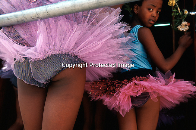 Dance students in the Dance for All program on November 25, 2000, waiting to enter the stage at a yearly performance in Guguletu, South Africa. The show is attended by a mixed crowd of relatives, friends and whites from more affluent areas in Cape Town. The program was started by the Cape Town City ballet in the poor and destitute squatter camps nine years ago. About 200 kids aged from 6-18 are dancing after school and finding something meaningful to do after school. .Photo: Per-Anders Pettersson/Agentur Focus