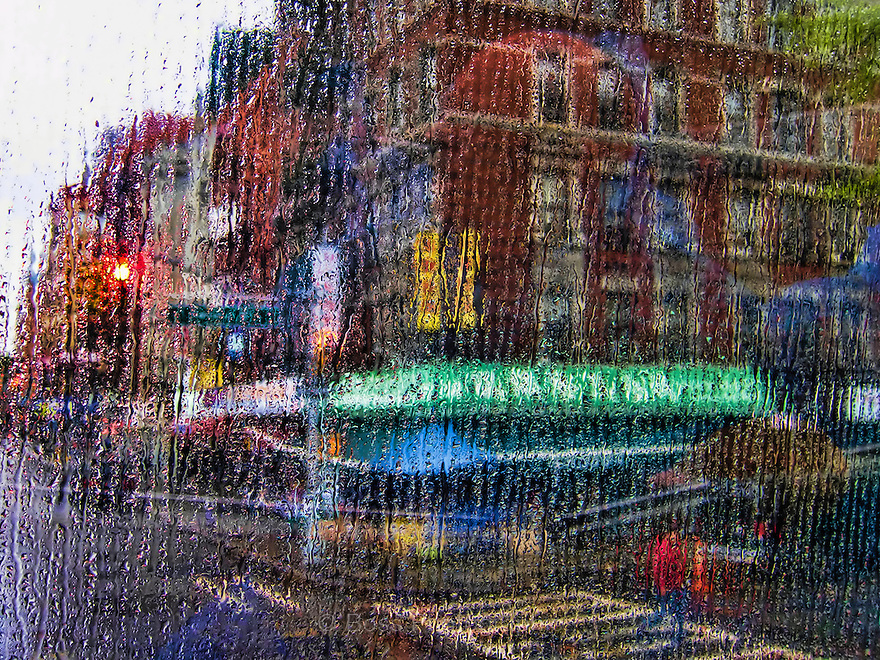 Abstract image of a New York street corner through a rain-streaked window