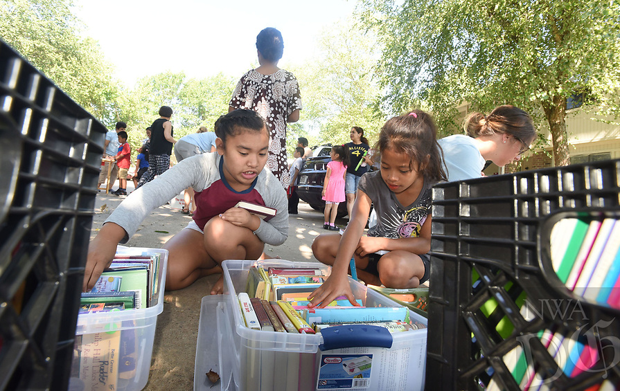 NWA Democrat-Gazette/FLIP PUTTHOFF<br />Damina Mea, 8 (left), and Ronitha Bungitak, 9, look through books Tuesday July 11 2017 provided by Tillery Elementary in Rogers for summer reading.