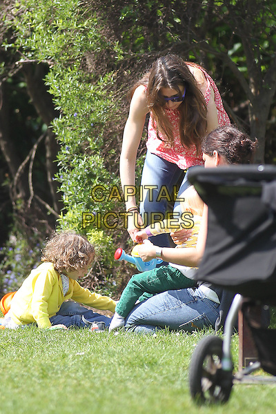 Jools Oliver and Buddy Bear in Primrose Hill, London, England..May 22nd, 2012.full length pink print top bending leaning jeans denim mother mom mum son kid child yellow top green trousers sunglasses shades .CAP/HIL.©John Hillcoat/Capital Pictures.