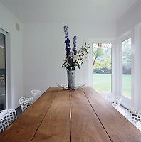 Knoll wire chairs and a wooden table designed by Deborah Berke in the enclosed porch