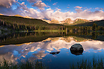 summer morning reflection at Sprague Lake with peaks of the Continental Divide on the horizon in Rocky Mountain National Park, Colorado, USA