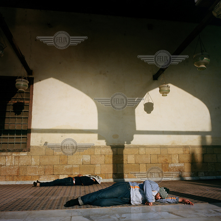 Two men sleep outside the Al Azar Mosque in Islamic Cairo.
