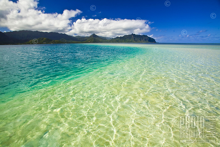 Crystal clear blue water and white sand at the Kaneohe Sandbar on the windward side of Oahu, with the Koolau Mountains in the background