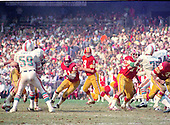 Washington Redskins quarterback Sonny Jurgensen (9) looks for a receiver during the game against the Miami Dolphins at RFK Stadium in Washington, DC on October 13, 1974.  Also pictured are Dolphins left linebacker Doug Swift (59), Redskins running back Larry Brown (43), Redskins right guard Walt Sweeney (78), Dolphins left defensive tackle Manny Fernandez (75), and Dolphins right defensive end Bill Stanfill (84).  The Redskins won the game 20 - 17.<br /> Credit: Arnie Sachs / CNP
