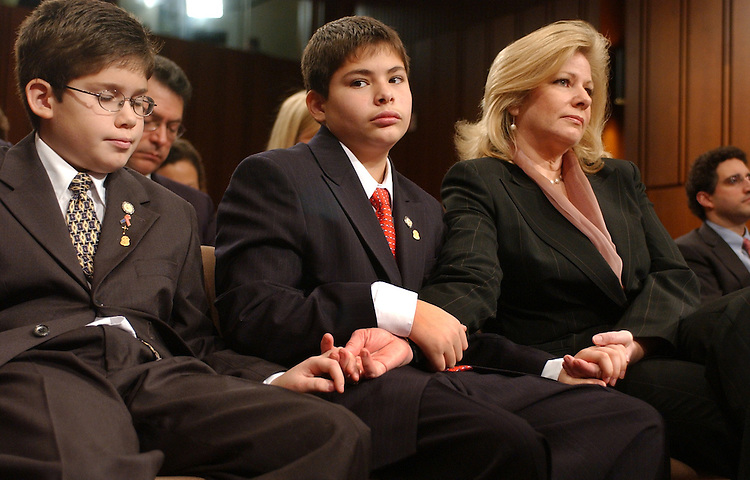 From left, Graham, 12, Gabriel Gonzales and their mother Rebecca Turner Gonzales, hold hands as their father Alberto Gonzales, is grilled by Sen. Ted Kennedy, D-Mass., during a hearing the Senate Judiciary Committee, on Gonzales' nomination for U.S. Attorney General.
