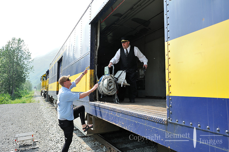 Nic Moir collects his rafting gear from brakeman Tony xxx. The Alaska Railroad's Spencer Glacier Whistlestop train gives visitors access to hiking, camping and stunning views.