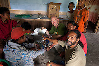 May 3rd 2012_ LACLUBAR, TIMOR-LESTE_ Daniel J. Groshong, Founding Director of The Hummingfish Foundation (background with green T-shirt) and residence of the mountain town of Laclubar, inspect a new hand pulping machine donated to them by The Hummingfish Foundation.  The pulper is part of an organic coffee farmer support project, designed to improve the farmer's coffee and create a high end brand as well.  Photographer: Daniel J. Groshong/The Hummingfish Foundation