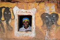 ANGOLA Kwanza Sul, village Cassombo, rural development project, woman looking out the window of her clay hut with wall paintings of animal  / ANGOLA Kwanza Sul, laendliches Entwicklungsprojekt ACM-KS, Dorf Cassombo, Frau Felismina Napitango 43 Jahre - NUR FÜR REDAKTIONELLE NUTZUNG, Kein PR !
