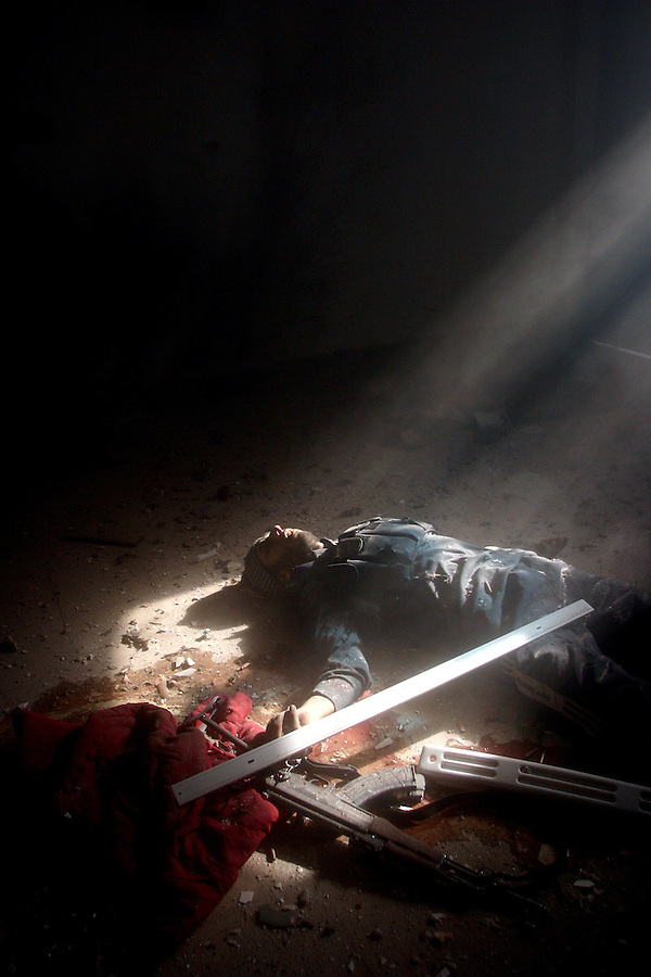The body of an insurgent lies on the floor of a home in western Fallujah after Marines with Kilo Co. (3/1) discovered him and two companions while searching city blocks house by house on Saturday, Nov. 13, 2004.  The death of the trio was only the beginning of a firefight in the house that lasted more than an hour and left one Marine and seven insurgents dead. Seven Marines were seriously wounded as Kilo Co. struggled to evacuate its casualties under fire.  Finally able to exit the building, combat engineers leveled the structure with 20 lbs. of high explosives in an effort to kill any fighters remaining inside. The fight in the home became known as the ?ell House?to Kilo Co. and marked a turning point in the way the company cleared the rest of their piece of the city. Afterward, when contact was made with the insurgents, the Marines called in bulldozers, C-4, and air strikes.