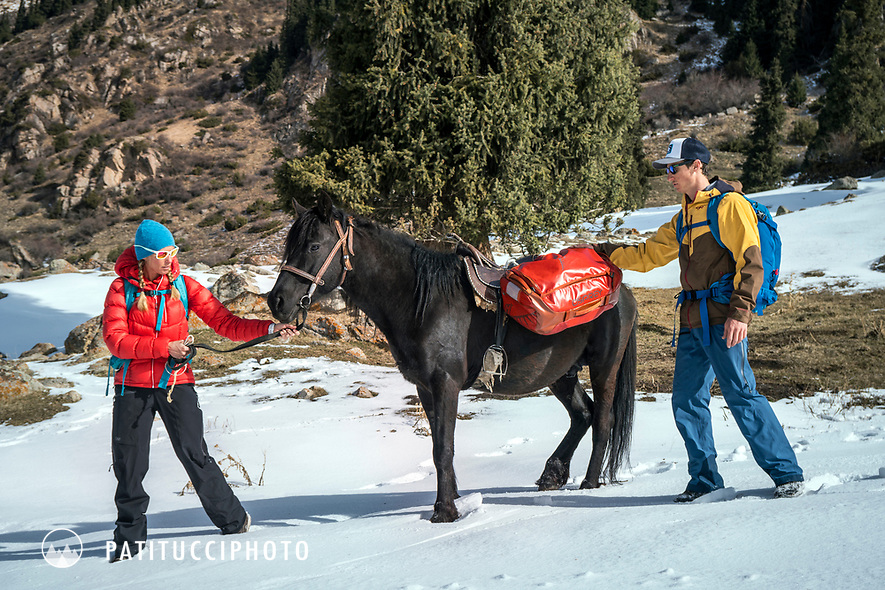 A couple with their pack horse loaded with duffel bags to go into a backcountry yurt camp in the Aksuu Valley of Kyrgyzstan