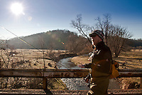 An angler on a bridge above a trout stream while fly fishing in the Driftless Area of southwest Wisconsin.