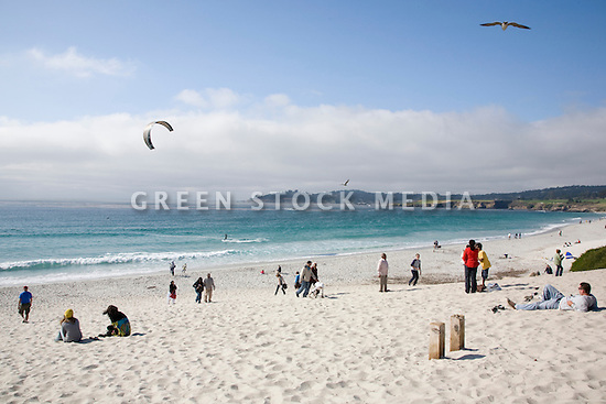 A large group of people relaxing and kitesurfing on Carmel Beach. Carmel, California, USA