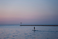 A stand up paddleboard paddler on Lake Superior at Grand Marais Michigan.