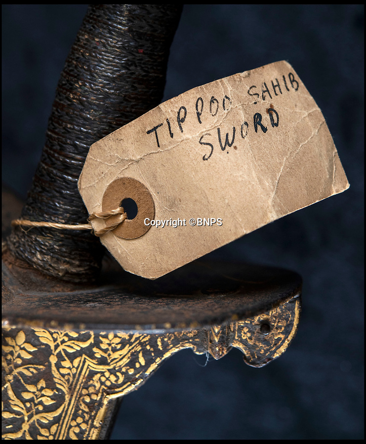 BNPS.co.uk (01202) 558833<br /> Pic: PhilYeomans/BNPS<br /> <br /> Contemporary label 'Tippoo Sahib sword'.<br /> <br /> Stunning artefacts from Indian hero Tipu Sultan's fateful last stand have been rediscovered by the family of an East India Company Major who took part in the famous battle that ended his reign.<br /> <br /> And now Major Thomas Hart's lucky descendents are likely to become overnight millionaires after retrieving the historic items from their dusty attic.<br /> <br /> The fascinating treasures were taken from Tipu's captured fortress of Seringapatam in the wake of his defeat by British forces led by a young Duke of Wellington in 1799.<br /> <br /> The cache of ornate gold arms and personal effects even include's the battle damaged musket the Sultan used in his fatal last stand against the expanding British Empire in India.<br /> <br /> Tipu was last seen on the battlements of the fortress firing his hunting musket at the advancing British and after the fierce encounter his body was found bearing many wounds, including a musket ball shot above his right eye.<br /> <br /> The rediscovered musket, complete with battle damaged bayonet, has the distinctive tiger stripe pattern unique to the self styled Tiger of Mysore own weapons - and tellingly there is also shot damage to the lock and stock that may have been caused by the musket ball that finished him off.<br /> <br /> Also included in the sale are four ornate gold-encrusted sword's bearing the mark of Haider Ali Khan, Tipu's father and the previous ruler of independent Mysore, along with a solid gold 'betel casket' complete with three 220 year old nuts still inside.<br /> <br /> The war booty was brought back to Britain by Major Thomas Hart of the British East India Company following the fourth and final Anglo-Mysore war.<br /> <br /> They have been passed down through the family ever since and now belong to a couple who have kept them wrapped in newspaper in the dusty attic of their semi-detached home for years.