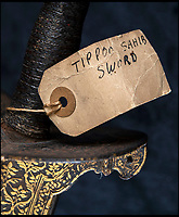 BNPS.co.uk (01202) 558833<br /> Pic: PhilYeomans/BNPS<br /> <br /> Contemporary label 'Tippoo Sahib sword'.<br /> <br /> Stunning artefacts from Indian hero Tipu Sultan's fateful last stand have been rediscovered by the family of an East India Company Major who took part in the famous battle that ended his reign.<br /> <br /> And now Major Thomas Hart's lucky descendents are likely to become overnight millionaires after retrieving the historic items from their dusty attic.<br /> <br /> The fascinating treasures were taken from Tipu's captured fortress of Seringapatam in the wake of his defeat by British forces led by a young Duke of Wellington in 1799.<br /> <br /> The cache of ornate gold arms and personal effects even include's the battle damaged musket the Sultan used in his fatal last stand against the expanding British Empire in India.<br /> <br /> Tipu was last seen on the battlements of the fortress firing his hunting musket at the advancing British and after the fierce encounter his body was found bearing many wounds, including a musket ball shot above his right eye.<br /> <br /> The rediscovered musket, complete with battle damaged bayonet, has the distinctive tiger stripe pattern unique to the self styled Tiger of Mysore own weapons - and tellingly there is also shot damage to the lock and stock that may have been caused by the musket ball that finished him off.<br /> <br /> Also included in the sale are four ornate gold-encrusted sword's bearing the mark of Haider Ali Khan, Tipu's father and the previous ruler of independent Mysore, along with a solid gold &lsquo;betel casket&rsquo; complete with three 220 year old nuts still inside.<br /> <br /> The war booty was brought back to Britain by Major Thomas Hart of the British East India Company following the fourth and final Anglo-Mysore war.<br /> <br /> They have been passed down through the family ever since and now belong to a couple who have kept them wrapped in newspaper in the dusty attic of their semi-detached home for years.