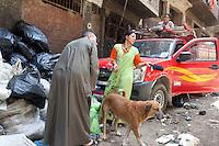 2011 Mokattam Garbage City (alla periferia del Cairo) il quartiere copto dove si vive in mezzo alla spazzatura raccolta: persone e un cane in una strada piena di sacchi dell'immondizia.