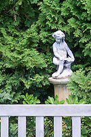 Cherub statute ornament in garden against evergreen shrubbery with matching color blue garden bench