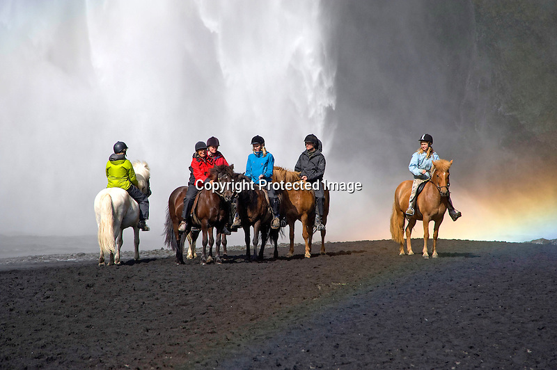 Riders on Icelandic Horses Enjoying Spray from Skogafoss Waterfall in South Iceland