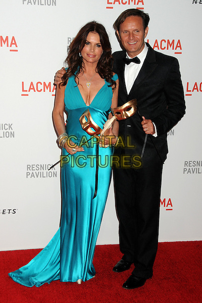 "ROMA DOWNEY & MARK BURNETT.LACMA's ""The Unmasking"" of the Lynda & Stewart Resnick Exhibition Pavilion Opening Gala held at the Los Angeles County Museum of Art, - Los Angeles, California, USA, 25th September 2010..full length blue turquoise dress long maxi mask cleavage clutch bag  black tuxedo tux bow tie .CAP/ADM/BP.©Byron Purvis/AdMedia/Capital Pictures."