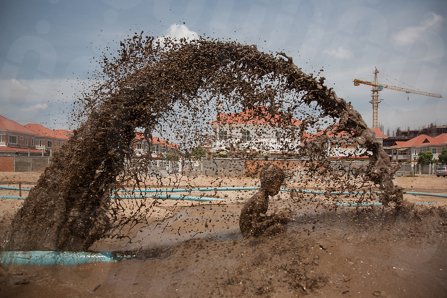 March 27, 2009 - Phnom Penh, Cambodia. A child plays in muddy water that is spraying out of a broken pipe, the pipes are pumping sand into a natural lake in Borei Reakreay community. The community was evicted from their homes in mid-2009 to make way for residential complexes. © Nicolas Axelrod / Ruom
