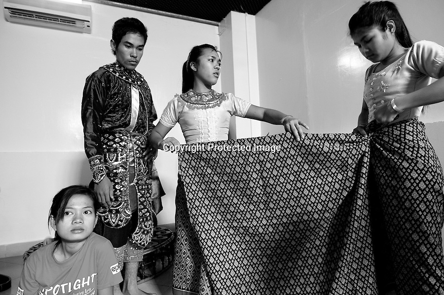 : Children of Bassac. In a building rented by Cambodian Living Arts, an association that helps Ieng Sithul students, the young women and men are trying on the costumes they have sewed themselves. Even if the children perform sometimes in restaurant or weddings, the reality is still tough, as Nop Thyda says : « the costumes cost 2 dollars each piece, we don't have the financial means to embroider it by someone else ». Phnom Penh, Cambodia - 2008